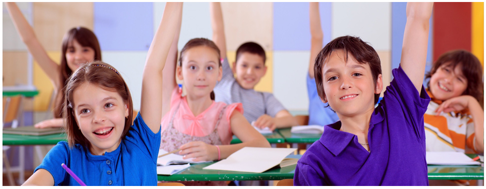Children in classroom, arms raised.